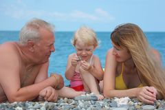 Mother and grandfather with child on sea coast Royalty Free Stock Images