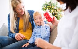 A mother and grandmother giving present to a small boy at home at Christmas time. A mother and unrecognizable grandmother giving presents to a happy small boy stock photo