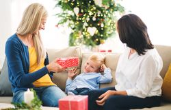 A mother and grandmother giving presents to a small boy at home at Christmas time. A mother and grandmother giving presents to a happy small boy at home at stock photos