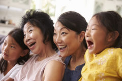 Mother With Grandmother And Granddaughters Watching TV Stock Photos