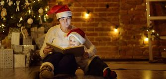 Mother or grandmother with her little son or grandson reading a magic book in cozy living room royalty free stock photos