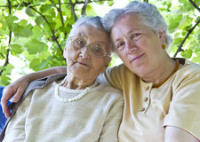 Mother and grandmother. Old mother and grandmother embracing in the garden Stock Photo