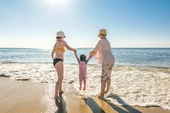 Mother and grandmother playing with child in the surf at the beach royalty free stock photography