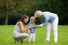 Mother and grandmother showing little girl flower. Portrait of a mother and grandmother showing little girl flower royalty free stock photo