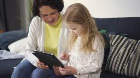 Mother or grandmother is sitting on sofa and showing to little girl digital technology