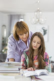 Mother guiding daughter in doing homework at table Royalty Free Stock Image