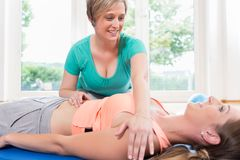 Mother in gymnastics course gets pregnancy recovery massage. Woman in postnatal gymnastics course gets pregnancy recovery massage stock image