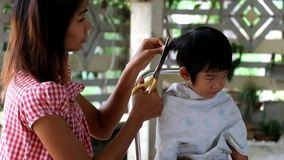 Mother hair dresses  her boy, mom hair dresses her kid son. son annoy mother cut his hair stock video footage