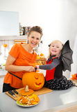 Mother with halloween dressed daughter carving Jack-O-Lantern Stock Image