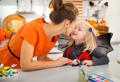 Mother with halloween dressed daughter in decorated kitchen Royalty Free Stock Image