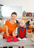 Mother with halloween dressed girl wearing oven mitts in kitchen Stock Images