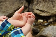 Mother hand and baby feet Stock Photos