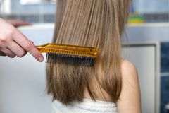 Mother hand with brush combing long fair hair of cute child girl after bath on blurred interior background stock photography