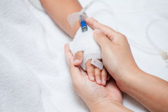 Mother hand holding child hand who have IV solution. In the hospital with love and care Royalty Free Stock Image