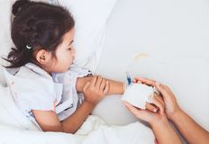 Mother hand holding sick daughter hand who have IV solution. Bandaged with love and care while she is sleeping on bed in the hospital Royalty Free Stock Image