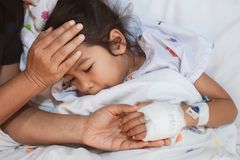 Mother hand holding sick daughter hand who have IV solution bandaged with love and care while she is lying down on bed. In the hospital stock image