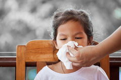 Mother hand holding tissue and help sick daughter wiping. And cleaning nose on black and white background Royalty Free Stock Photos