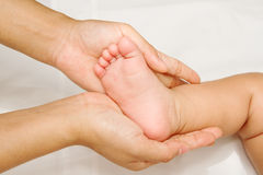 Mother hand massaging foot of her baby Stock Photo