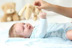 Mother hand playing with her baby son. Mother hand holding a teddy and playing with her baby son on a bed royalty free stock photography