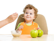 Mother hand spoon feeding baby Stock Images