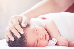 Mother hand touching asian newborn baby girl head. While she sleeping with tenderness in vintage color tone stock image
