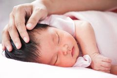 Mother hand touching asian newborn baby girl head Royalty Free Stock Photos