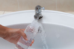 Mother hand washing baby milk bottle on white sink Royalty Free Stock Photos