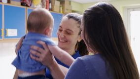 Mother handing baby son to female nursery worker stock footage