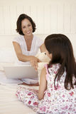 Mother Handing Teddy Bear To Daughter On Bed Stock Photos