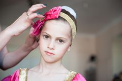 Mother hands correct hat of young cute russian dancer ballerina girl indoors royalty free stock photo