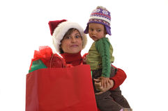 Mother hands full. Young mom in santa hat, holding bags with presents and a kid Stock Photo