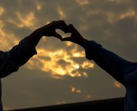 Mother hands and heart-shaped son that light shines through. It stock images