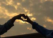 Mother hands and heart-shaped son that light shines through. It stock photography