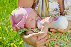 Hands hold baby and feed him from bottle Stock Photos