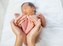 Mother hands hold little newborn baby feet with love emotion and the baby is sleeping on white bed royalty free stock photos