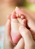 Mother hands holding infant baby foot Royalty Free Stock Image