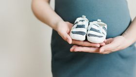 Mother hands holding shoes for the newborn baby. Pregnant woman touching belly. Happy woman pregnancy, maternity, body care. Pregnant woman touching belly stock image
