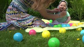 Mother hands put cap on unhappy baby daughter head in outdoor park. 4K stock footage