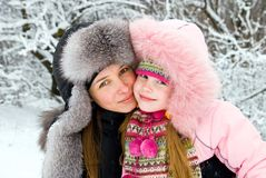 Mother happiness. Young mother and daugther in winter clothing hugging in a winter woods Royalty Free Stock Photo