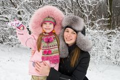 Mother happiness. Young mother and daugther in winter clothing hugging in a winter woods Royalty Free Stock Photography