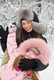 Mother happiness. Young mother and daugther in winter clothing in a winter woods Royalty Free Stock Images