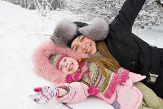Mother happiness. Young mother and daugther in winter clothing hugging in a winter woods Stock Image