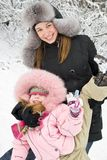 Mother happiness. Young mother and daughter in winter clothing in a winter woods Stock Photo