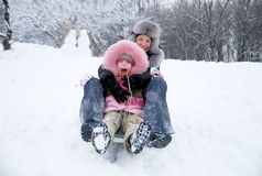 Mother happiness. Young mother and daughter in winter clothing in a winter woods Stock Photos