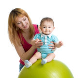 Mother with happy baby doing exercises with gymnastic ball. Concept of caring for children health. Mother with happy baby doing exercises with gymnastic ball Royalty Free Stock Photography