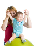 Mother with happy baby doing exercises with gymnastic ball. Concept of caring for kids health. Mother with happy baby doing exercises with gymnastic ball Stock Photo
