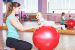 Mother with happy baby doing exercises with gymnastic ball Royalty Free Stock Photography