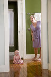 Mother with happy baby sitting on floor at home stock image