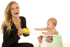 Mother happy feeding baby. A mother with a big smile, laughing while her baby is reaching out for more food Royalty Free Stock Photo