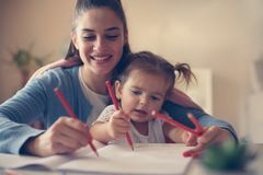 Mother and happy girl playing and writing together stock image